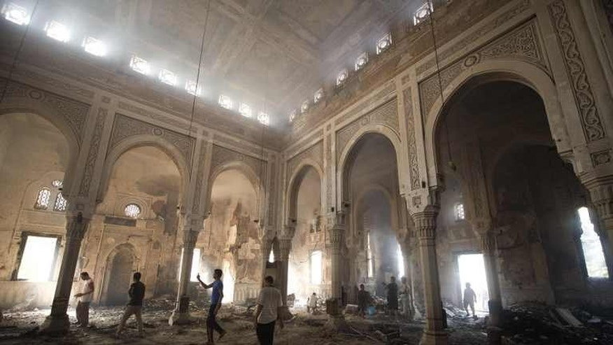 "Residents walk through debris and rubble inside the burnt down mosque of Rabaa al-Adawiya on August 15, 2013 in Cairo, Egypt. Just two years ago, Egypt's Muslim Brotherhood won the country's first free elections, but now many in the country call its supporters ""terrorists."""