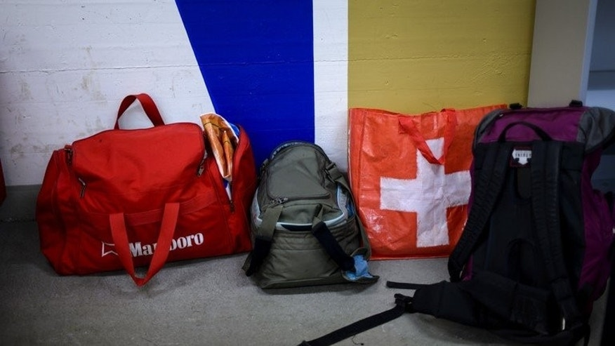 Bags belonging to asylum seekers, one bearing the Swiss national flag, in a subterranean shelter used as temporary asylum center on August 14, 2013 in Kestenholz. Some Swiss cantons are demanding systematic DNA tests on asylum seekers -- specifically Eritreans -- who say they are coming to the country to join family members, a newspaper reported Sunday.