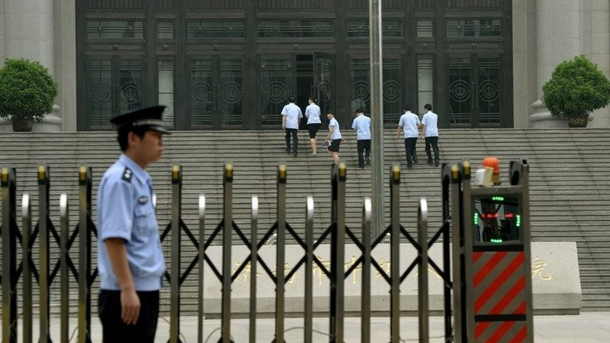 Police stand guard outside the Intermediate People's Court where Chinese politician Bo Xilai was indicted and his case expected to be heard in Jinan, Shandong Province on July 25, 2013. China's former top economic policymaker Liu Tienan has been placed under judicial investigation for suspected bribe taking, state media reported on Sunday.