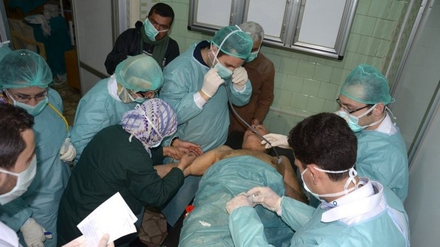 In this image made available by the Syrian News Agency (SANA) on March 19, 2013, medics and other masked people attend to a man at a hospital in Khan al-Assal in the northern Aleppo province, as Syria's government accused rebel forces of using chemical weapons for the first time. UN inspectors tasked with investigating whether chemical weapons have been used arrived in Damascus Sunday.