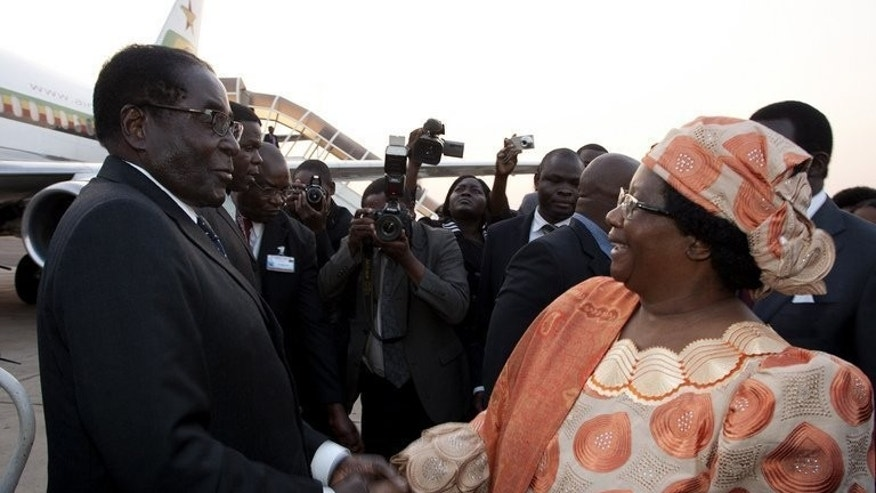 Malawi President Joyce Banda welcomes Robert Mugabe at Kamuzu Airport in Lilongwe on Friday. Mugabe will be sworn in on Thursday, beginning a fresh five-year mandate as Zimbabwe's president following a disputed election, his spokesman said Sunday