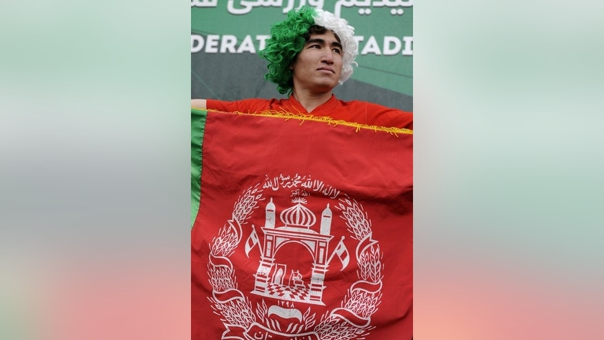 A football fan holds the Afghan flag during the final game of the Afghan Premier League in Kabul on October 19, 2012. Tuesday's game will be followed on Thursday by the start of the second season of the Afghan Premier League.