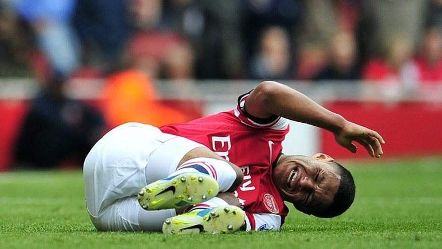 Alex Oxlade-Chamberlain lies on the grass after a clash with Antonio Luna at The Emirates on Saturday. Arsenal are facing an early season injury criris and the winger could be out of action for the best part of six months, the Daily Mail reported on Monday.