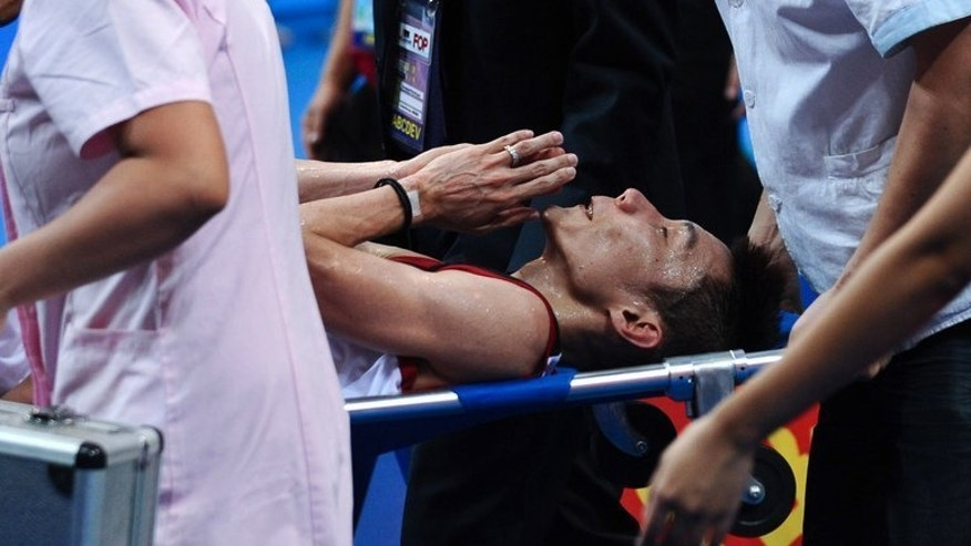 Malaysia's Lee Chong Wei is carried away after injury during his match against China's Lin Dan on August 11, 2013. Lin Dan said a decision to switch off air conditioning was not controversial as both players were faced with the same conditions.