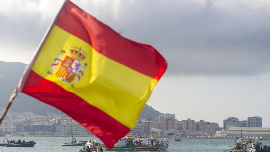 A fisherman holds a Spanish flag during protest in the bay of Algeciras on August 18, 2013. British frigate HMS Westminster docked in Gibraltar in a naval exercise coinciding with a furious diplomatic row with Spain over sovereignty and fishing rights in the surrounding waters.