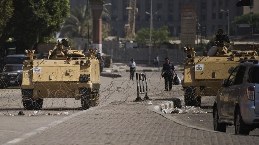 Army armoured personnel carriers at the entrance to Cairo's Tahrir Square on Sunday. The dusk-to-dawn curfew was declared on Wednesday, as hundreds were killed after police moved to clear two protest camps set up by loyalists of ousted Islamist president Mohamed Morsi.