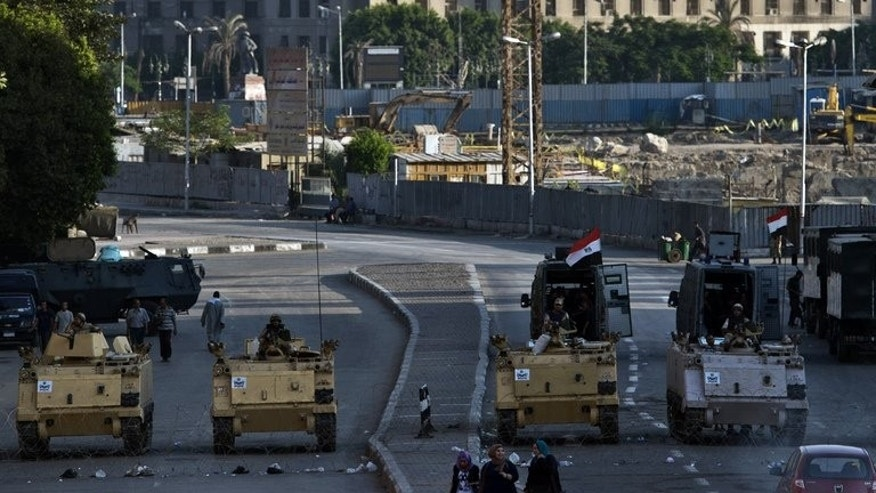 Army armoured personnel carriers in front of the Egyptian Museum in Cairo's Tahrir Square on Sunday. Main roads usually choked with rows of cars that far outnumber the lanes allotted to them stand empty after the curfew starts at 7:00pm.