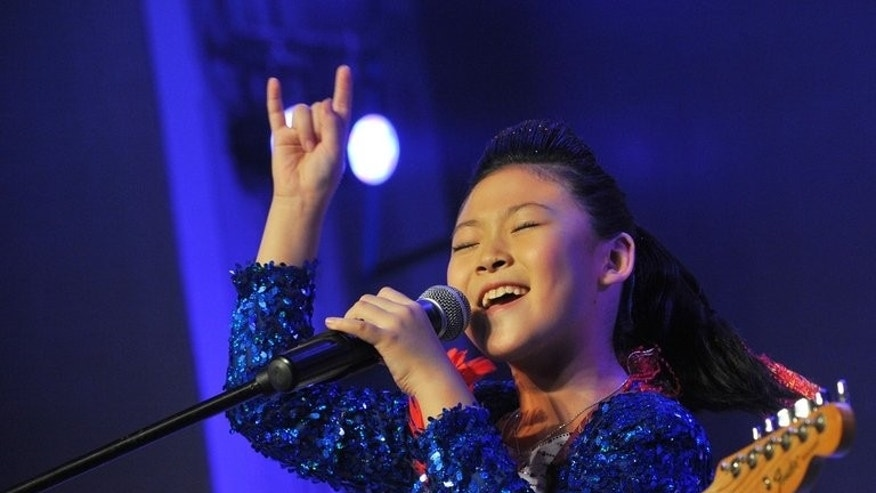 Zhou Zi performs with her band Cool at a children's rock competition in Tianjin, China, on August 11, 2013. She says she likes to play 'loud music that annoys old people'.