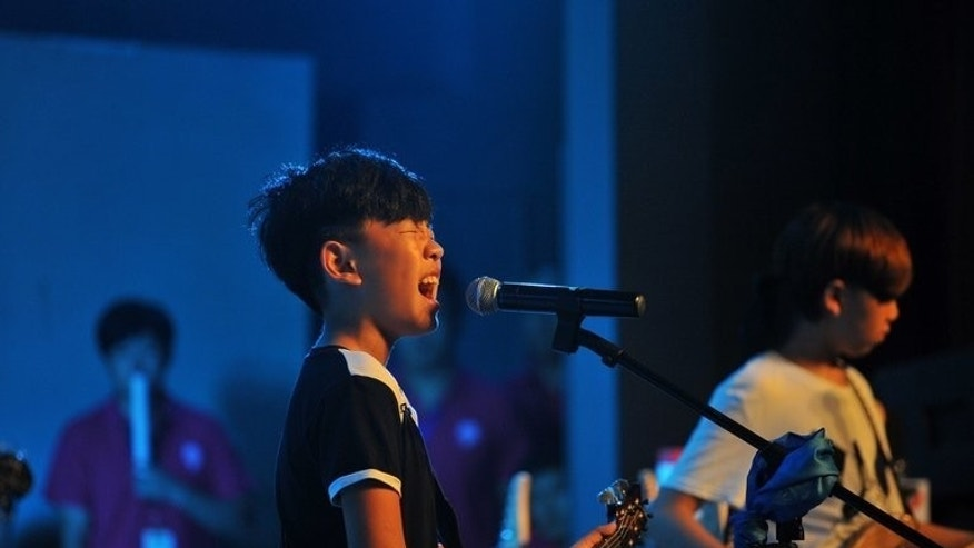 A boy sings and plays guitar at a children's rock competition in China on August 11, 2013. The county's first homegrown rock acts started performing in the 1980s when the Communist Party relaxed cultural controls.