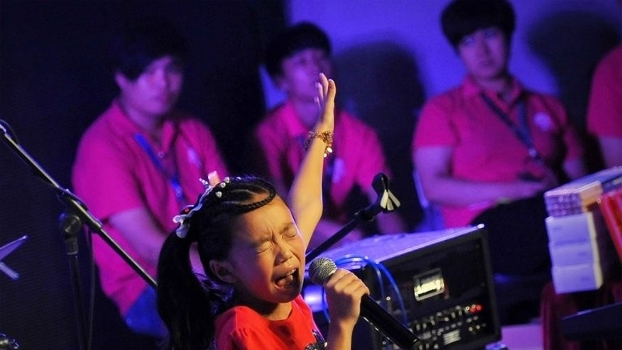 A girl performs during a children's rock competition in Tianjin, China, on August 11, 2013. Rather than throwing TVs out of windows and trashing their dressing rooms, the performers were happier playing hide and seek backstage.