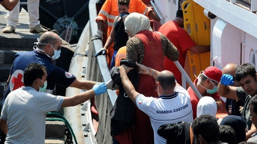 Coast guard help immigrants on August 19, 2013 in the Catania harbor after being rescued off the Italian coast. Four boats carrying more than 350 migrants including Egyptians and Syrians have landed in Italy, officials said Monday, the latest arrivals due to the growing unrest in north Africa.