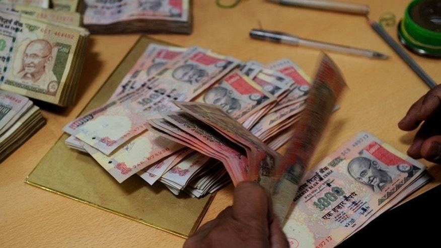 A man counts Indian rupee notes at a bank in Mumbai on May 16, 2012. India's rupee hit a new low and shares slipped another 1.3% on Monday on growing fears about the country's slowing economy.