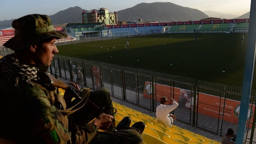 An Afghan security guard keeps watch as Pakistan football players train at the Afghanistan Football Federation (AFF) stadium in Kabul on August 19, 2013. Football fans in Afghanistan on Tuesday eagerly awaited the country's first home international in ten years, with their team set to take on neighbouring arch-rivals Pakistan in Kabul.
