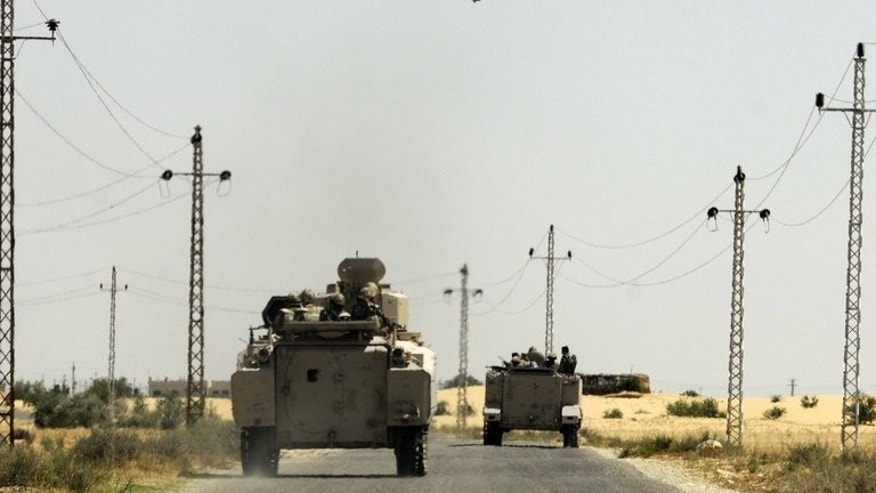 Egyptian soldiers and a military helicopter are seen in the area near the Rafah border crossing, on May 21, 2013. Militants fired rocket-propelled grenades at two buses packed with Egyptian policemen in Sinai, killing 24 in the deadliest attack of its kind in years.