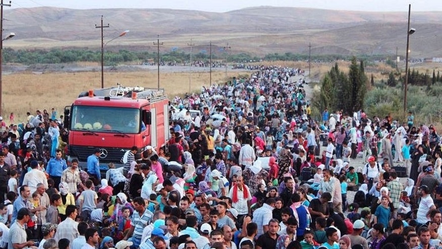 A handout photo obtained from the UNHCR on August 18, 2013 shows thousands of Syrians streaming into the autonomous Kurdish region of northern Iraq on August 15.