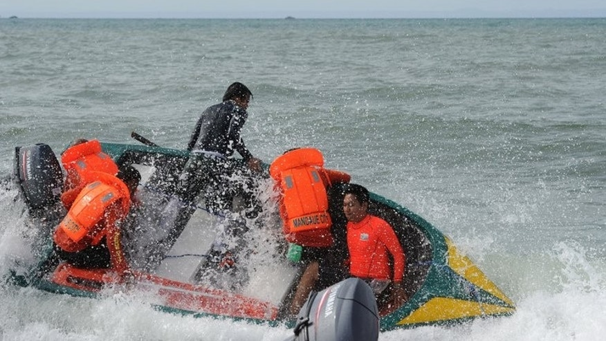 Volunteer rescuers struggle in big waves as they head to the site of a ferry crash near Cebu on August 18, 2013. The death toll from the disaster rose to 52 on Monday as more bodies were pulled from the water, the coastguard said.