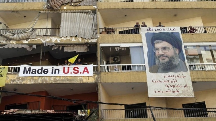 "People hang a poster of Hassan Nasrallah, head of Lebanon's militant Shiite Muslim movement Hezbollah on August 16, 2013. A radical Lebanese Sunni Muslim cleric said Monday a car bombing in a Beirut stronghold of Hezbollah was ""a natural result"" of the Shiite group's involvement in Syria's war."