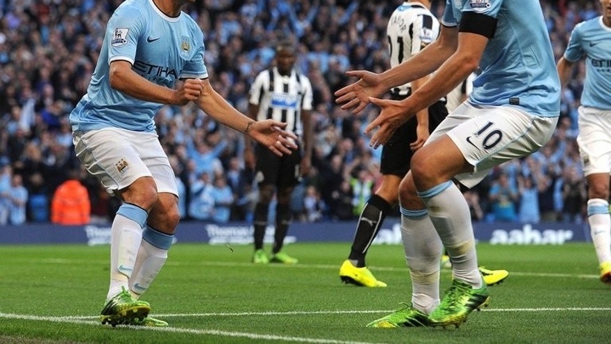 Manchester City's Spanish midfielder David Silva (L) celebrates with Manchester City's Bosnian forward Edin Dzeko after scoring the opening goal during the English Premier League football match between Manchester City and Newcastle United at The Etihad stadium in Manchester, northwest England, on August 19, 2013. City won 4-0.