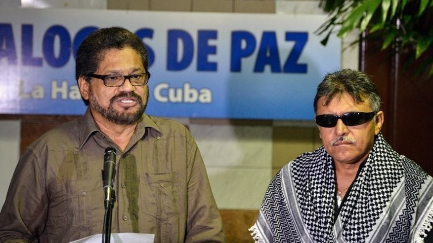 Revolutionary Armed Forces of Colombia (FARC) commander Ivan Marquez (L), gives a speech next to FARC Commander Jesus Santrich, at the Convention Palace in Havana as peace talks with the Colombian government resume on August 19, 2013. FARC, Colombia's largest guerrilla group, said it supported farmworker protests as it began a new round of peace talks.