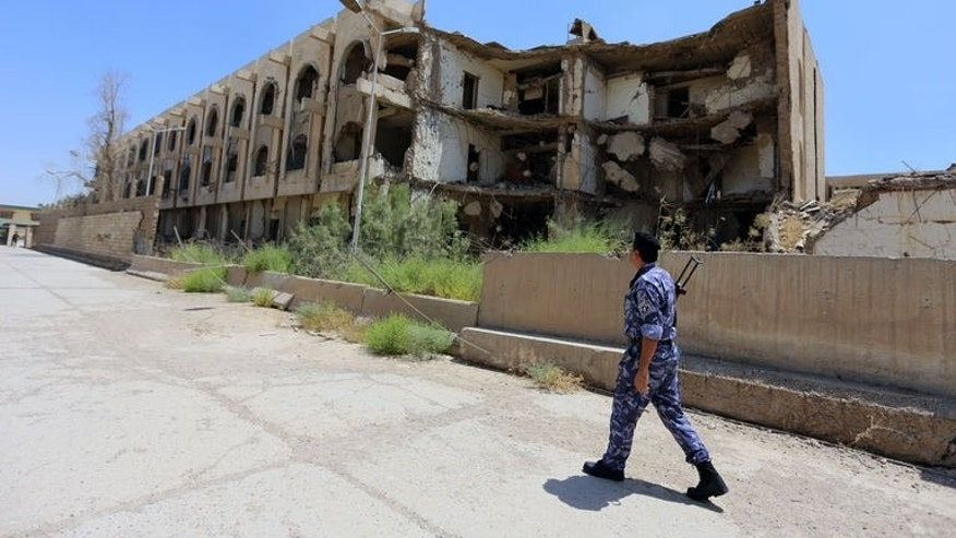 A security officer walks past the destroyed building of the former United Nations headquarters in Baghdad, on August 16, 2013, a decade after a massive bombing killed 22 people and drove heightened security measures that ultimately limited interactions with ordinary Iraqis.