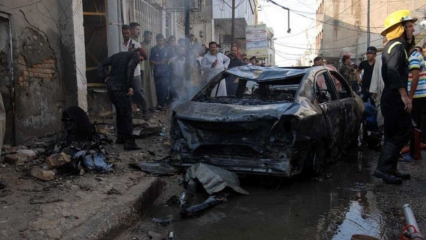 A picture taken on August 19, 2013 shows people gathering near the remains of a vehicle at the scene of a car bomb explosion in Nasiriyah, south of the Iraqi capital Baghdad. A policeman and two civilians were killed in bombings Tuesday, officials said, and 16 militants died as security forces conducted wide-ranging operations to combat the country's worst violence since 2008.