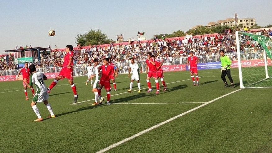 Afghanistan footballers (in red) compete with Pakistan players (in green) during a match in Kabul stadium on August 20, 2013. Afghanistan's football team sparked rowdy celebrations across the war-battered nation after securing an convincing 3-0 win over arch-rivals Pakistan in the first international match in Kabul for ten years.