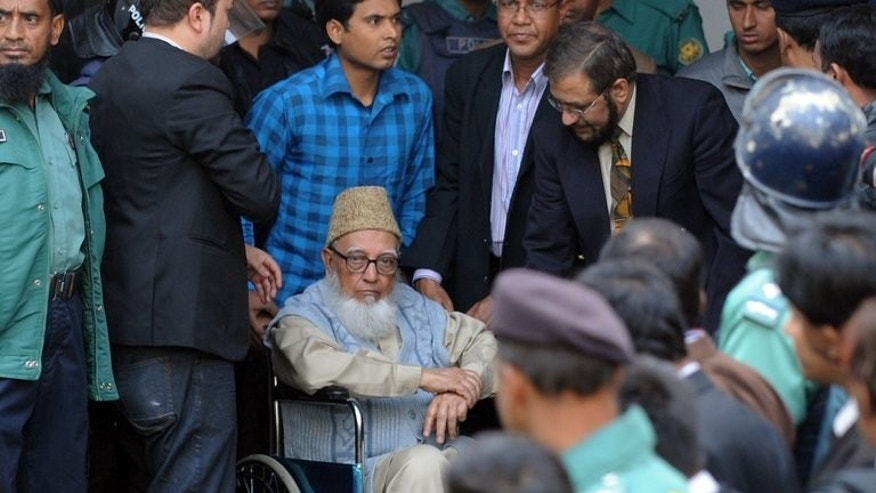 Former head of opposition Jamaat-e-Islami party Ghulam Azam (C) escorted by security personnel and lawyers as he emerges from the Bangladesh International Crimes Tribunal in Dhaka on January 11, 2012. Prosecutors at Bangladesh's war crimes tribunal Tuesday sought a contempt order against New York-based Human Rights Watch (HRW) over a report criticising a verdict against Azam.