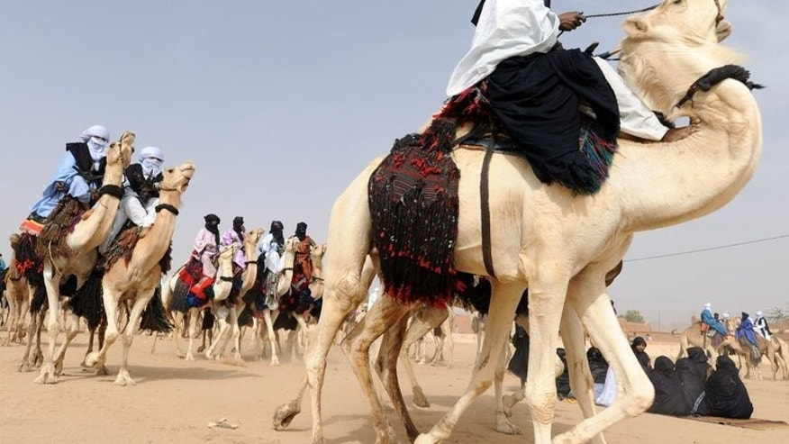 Tuareg men ride camels during the annual economic festival of Assihar in Tamanrasset on April 4, 2011. Deadly clashes between Arabs and Tuareg raged on into a second week in an Algerian border town on Tuesday, with another eight people killed, Algerian media reported.