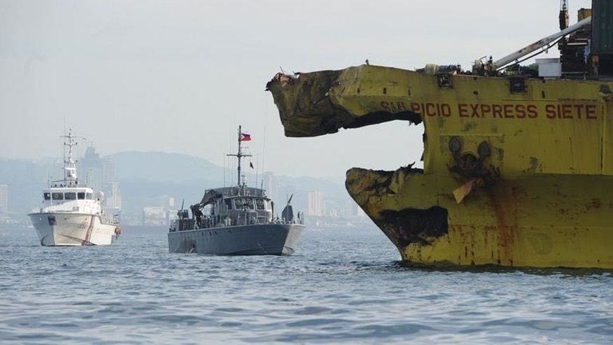 A Philippine Coast Guard ship (L) and navy patrol boat (C) anchored next to a damaged cargo ship on August 17, 2013 after it collided with the ferry St. Thomas Aquinas near the central city of Cebu. The confirmed death toll from the ferry disaster rose to 64 on Tuesday as more bodies were found, some of them inside the sunken ship itself.