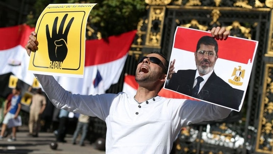 "A protester holds a placard reading ""R4BIA"" (L) and a poster of Egypt's ousted president Mohamed Morsi during a protest gathering about two hundreds people against army-installed Egyptian government, in front of the Saudi Arabia's embassy in Paris, on August 20, 2013."