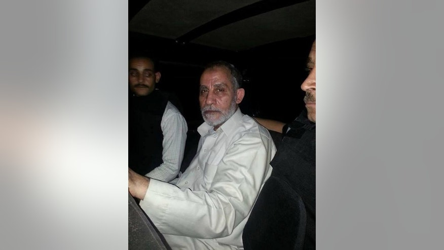 A picture distributed by the Egyptian police allegedly shows members of Egypt's security forces escorting Mohamed Badie (C), the supreme guide of the Muslim Brotherhood, following his arrest in the early hours of August 20, 2013 in Cairo's Nasr City district.