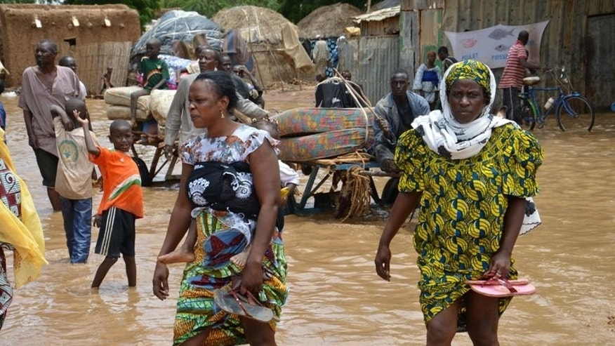 Local residents walk in the floodwaters as they evacuate Niamey after their homes were destroyed by floods on August 19, 2012. Severe flooding in drought-prone Niger has killed at least eight people, including seven children, and left around 2,000 homeless, authorities said Tuesday.
