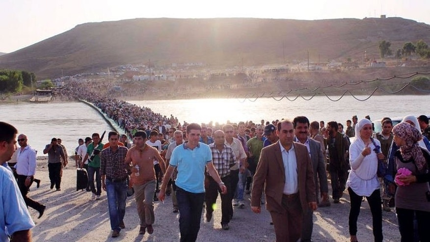 Photo obtained from the UNHCR on August 18, 2013 shows thousands of Syrians streaming across a bridge over the Tigris River and entering the autonomous Kurdish region of northern Iraq on August 15. Iraqi Kurdistan has slapped a limit of 3,000 a day on refugees entering from Syria, after more than 30,000 flooded in from their war-torn homeland in a matter of days, aid agencies said Tuesday.