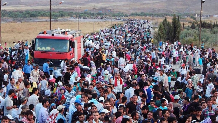 Photo obtained from the UNHCR on August 18, 2013 shows thousands of Syrians streaming into the autonomous Kurdish region of northern Iraq on August 15. Iraqi Kurdistan has slapped a limit of 3,000 a day on refugees entering from Syria, after more than 30,000 flooded in from their war-torn homeland in a matter of days, aid agencies said Tuesday.