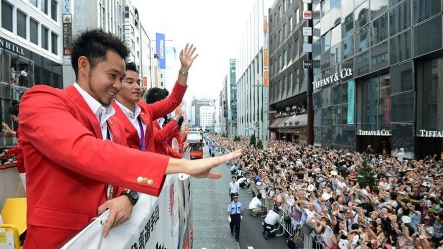 Kosuke Kitajima (L) waves to crowds of people from an open-top bus during a parade by Japan's 2012 London Olympic Games medallists at Tokyo's upmarket Ginza street on August 20, 2012. Kitajima is hoping a wave of public support will help Tokyo secure the 2020 Olympics as he contemplates the end of his glittering career.