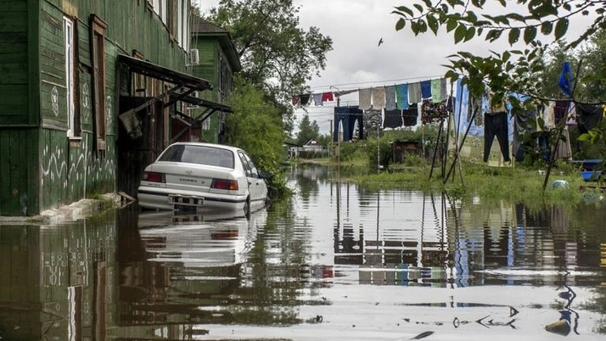 This picture taken on August 19, 2013 shows a car in a flooded street in the village of Bolshoi Ussuriysky island close to city of the Khabarovsk in Russia's Far Eastern Amur region.