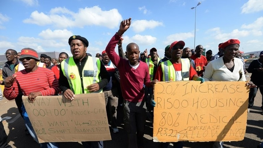 Workers on strike hold placards asking for wage increases as they demonstrate outside Ford's plant in Pretoria on August 20, 2013. More than 30,000 workers in South Africa's auto industry vowed to intensify an nationwide wage strike that has crippled a multi-billion dollar export market.