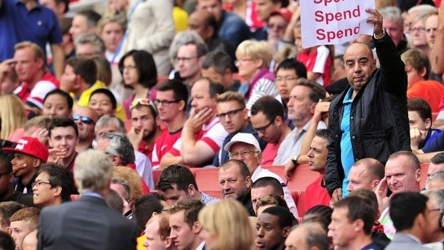 "An Arsenal fan holds up a poster bearing the message ""spend, spend, spend"" to Arsenal's French manager Arsene Wenger (L) during the match against Aston Villa in London on August 17, 2013."