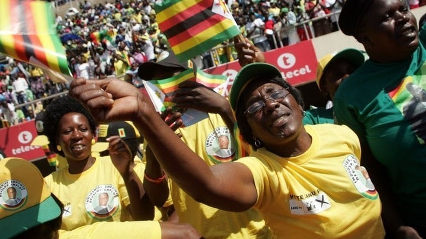 Supporters of Zimbabwe's President Robert Mugabe wave flags upon his arrival at the commemoration of Defence Forces Day in Harare on August 13, 2013. Zimbabwe's constitutional court on Tuesday ruled that a disputed elections which handed Robert Mugabe five more years in power were free and fair, dismissing allegations of vote-rigging.