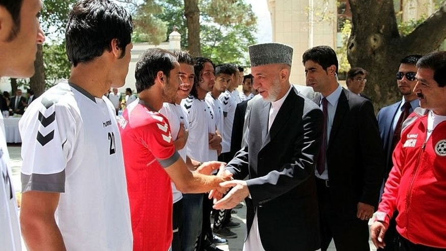 In this handout photograph released by the Presidential Palace, Afghan President Hamid Karzai (C) meets members of the Afghan national football team at the Presidential Palace in Kabul on August 21, 2013.