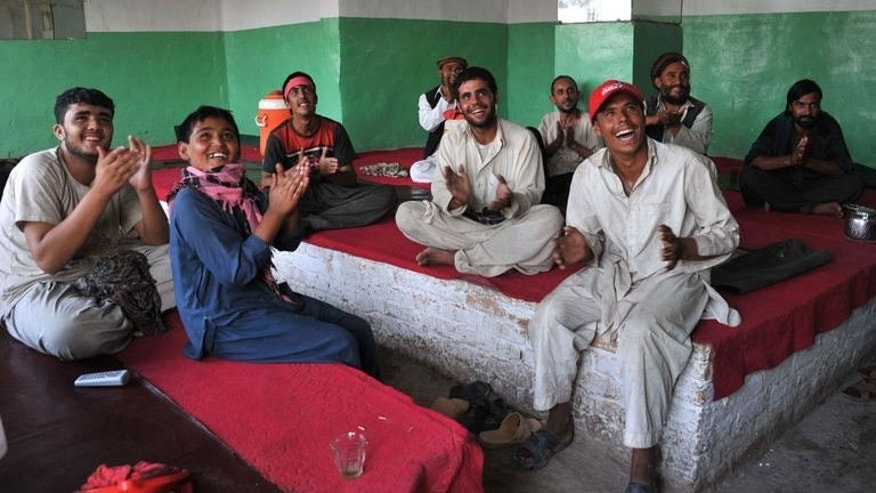Afghan young men watch the football match between Afghanistan and Pakistan in Jalalabad on August 20, 2013. Afghanistan's football team sparked rowdy celebrations across the war-battered nation after securing an convincing 3-0 win over arch-rivals Pakistan in the first international match in Kabul for ten years.