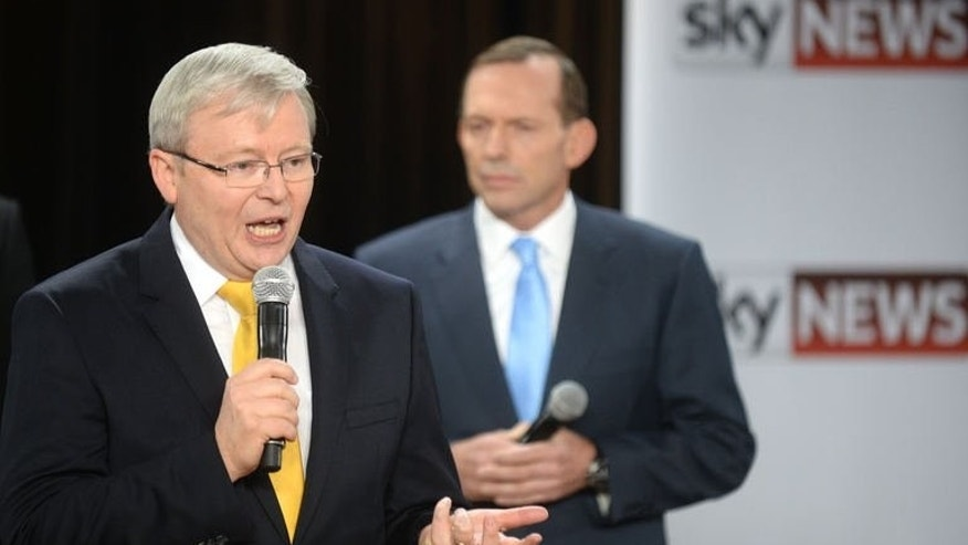 Australia's Prime Minister Kevin Rudd (L) speaks as oppostion leader Tony Abbott (R) listens during a people's forum in Brisbane on August 21, 2013. Rudd Wednesday used a televised forum to confront his election rival Tony Abbott on spending, demanding the opposition leader reveal where he would make cuts if elected.