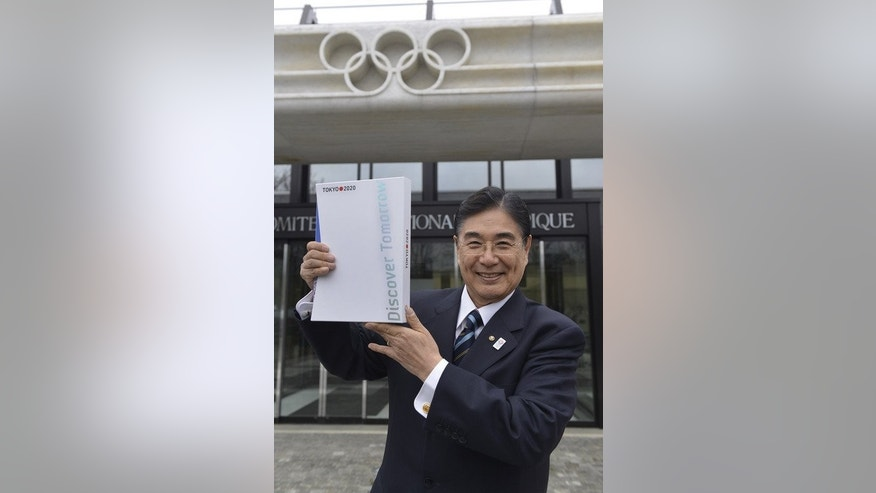 Masato Mizuno, CEO of the Tokyo 2020 Bid Committee, poses with the candidature files at the headquarters of the International Olympic Committee in Lausanne, on January 7, 2013.