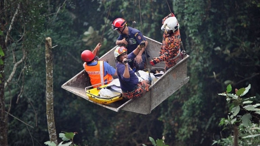 Malaysian rescuers help a passenger (C) after a bus carrying tourists and local residents fell into a ravine near the Genting Highlands, about an hour's drive from Kuala Lumpur on August 21, 2013. The bus that plunged into a ravine, killing 37 in Malaysia's worst-ever road accident, was overloaded according to reports