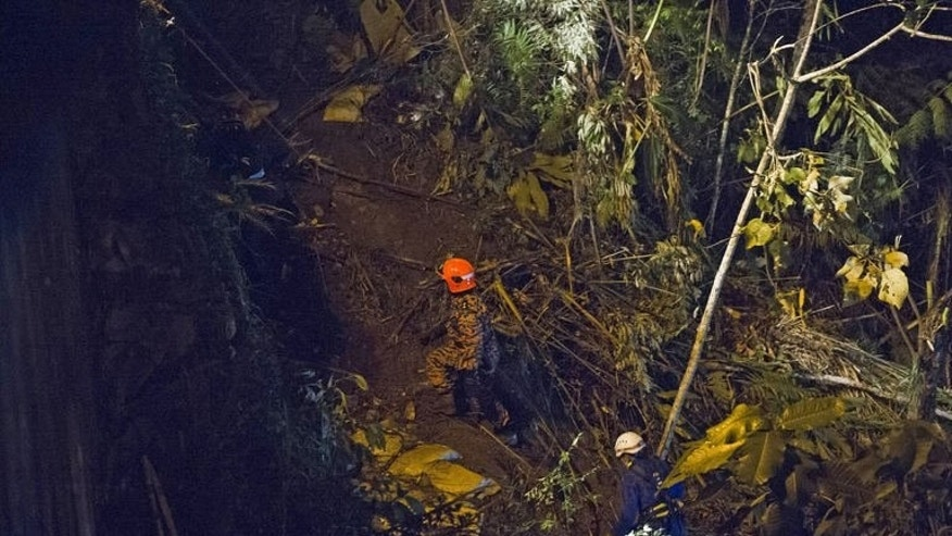 Malaysian rescuers search for passengers after a bus carrying tourists and local residents fell into a ravine near the Genting Highlands, on August 21, 2013. Malaysian media said Chinese, Indonesian, Bangladeshi and Thai nationals were believed to be among the dead and injured.