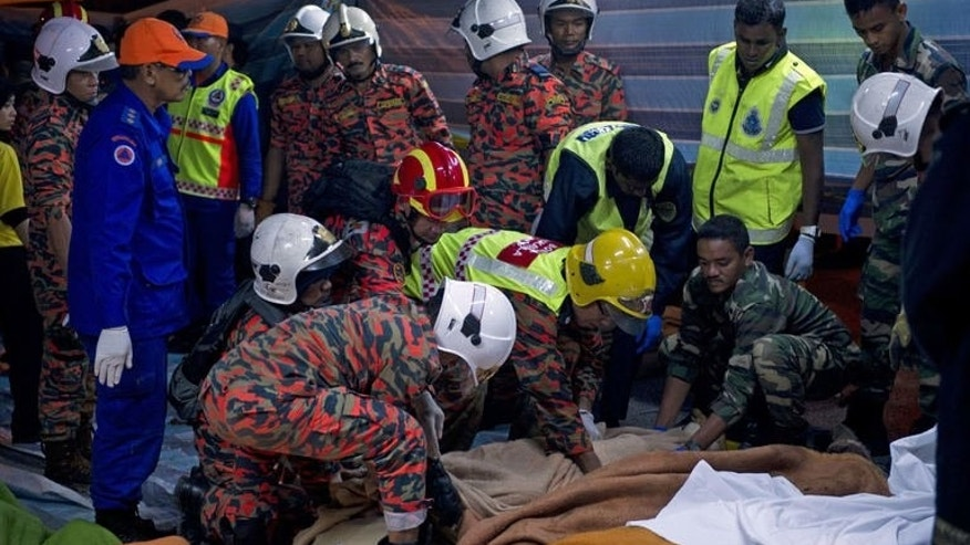 Malaysian rescuers attend to the bodies of bus passengers killed in an accident near the Genting Highlands, on August 21, 2013.