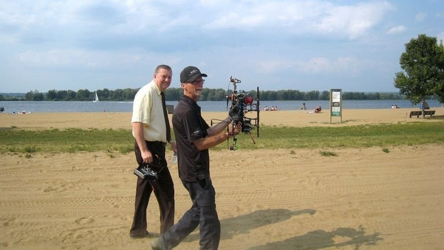"Ottawa city councilor Bob Monette (L) and Steve Wambolt, the owner of a hexacopter walk along a beach at Petrie Island park in Ottawa, Canada during a demonstration flight on August 21, 2013. ""I didn't know anything about geese before, and now I'm an expert,"" Wambolt said. For example, he said, geese don't like black, silver or bright orange colors, similar to predators or hunters' vests."