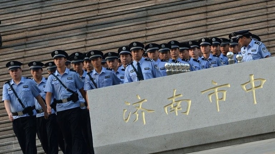 Police march outside the Intermediate People's Court where disgraced politician Bo Xilai will soon go on trial in Jinan, Shandong Province on August 21, 2013.