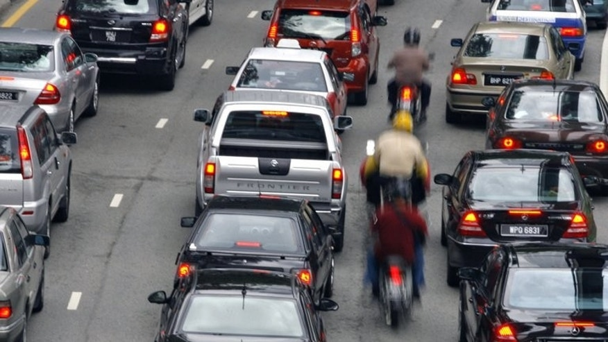 Motorcyclists ride in-between lanes to beat congestion during lunch-hour traffic in downtown Kuala Lumpur, December 19, 2006. A bus carrying up to 45 people plunged into a deep ravine near a Malaysian mountaintop tourist resort Wednesday, police said, but added they had no information yet on casualties.