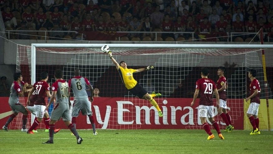 Zeng Cheng (C) of Evergrand Guangzhou makes a save from a Lekhwaya attempt during their quarter-final football match of AFC Champions League in Guangzhou on August 21, 2013. Evergrand Guangzhou won 2-0.